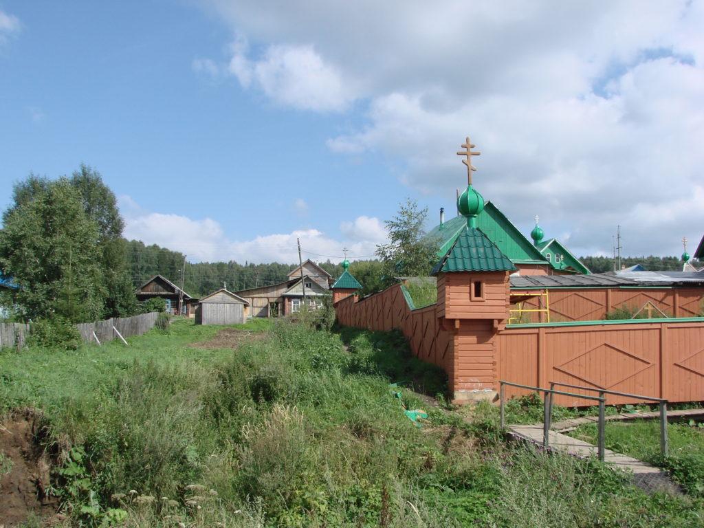 Ограда обители соседствует с деревенским пейзажем